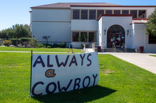 """A woman walks behind a sign that reads """"always a cowboy"""" that is placed near the Salinas High's admissions office on Tuesday, April 28, 2020."""