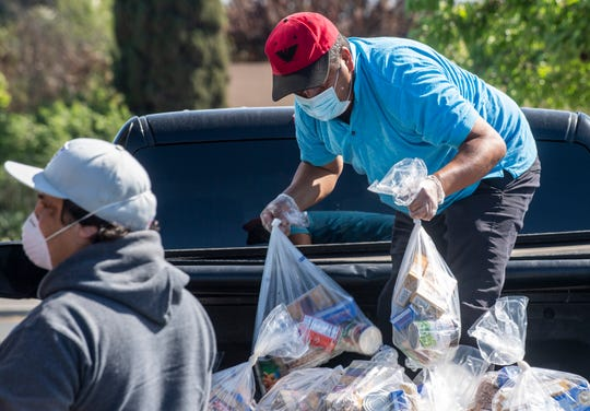 Martin Alvarez, holds two bag full of food items during the South County Food Distribution event in Soledad, Calif, on Friday, April 24, 2020.