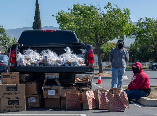 Soledad residents wait for food bags and other essential utilities during the South County Food Distribution event in Soledad, Calif, on Friday, April 24, 2020.
