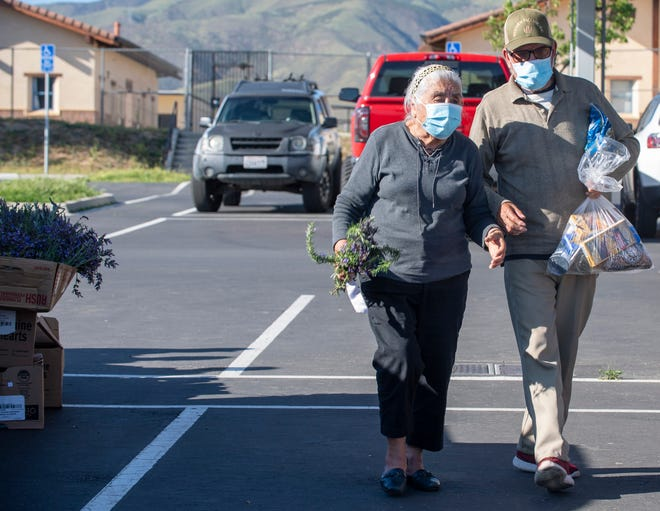Maria Sanchez, left, and her husband Jose Sanchez pick up a bouquet of lavender for her birthday during the South County Food Distribution event in Soledad, Calif, on Friday, April 24, 2020.