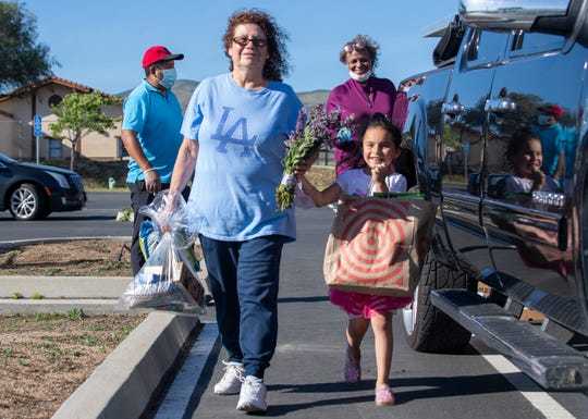 A woman holds her granddaughter's hand as they carry local produce, flowers, candy and toiletries during the South County Food Distribution event in Soledad, Calif, on Friday, April 24, 2020.