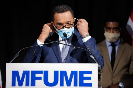 Democrat Kweisi Mfume removes a face mask before addressing reporters during an election night news conference after he won the 7th Congressional District special election, Tuesday, April 28,  in Baltimore.