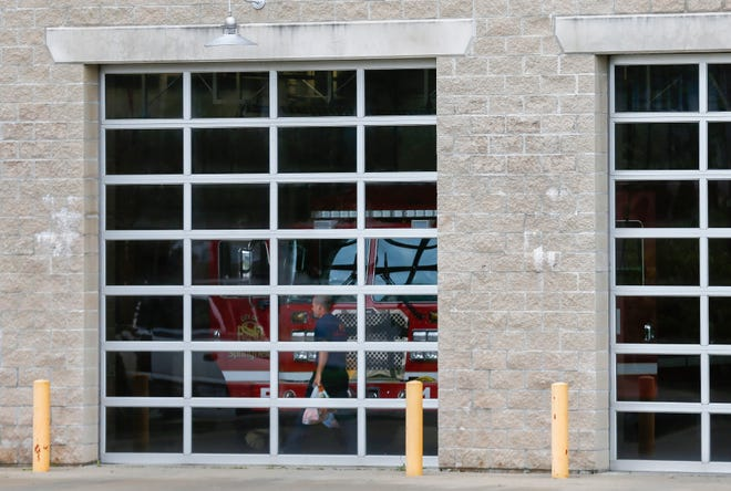 A firefighter carries bags into Springfield Fire Station 1 on Wednesday. The fire department has closed its stations to the public during the coronavirus pandemic.