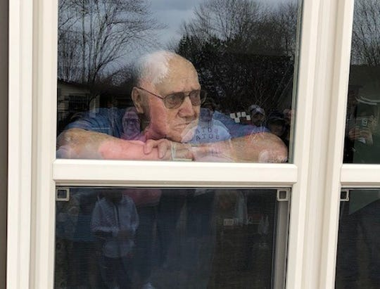 Hobbie Schleicher watches family members who surprised him and wife, Carol, for their 70th anniversary Saturday, April 18, 2020 at Serenity Place on Seventh in St. Joseph. The assisted living facility is not allowing visitors inside the building due to the pandemic.