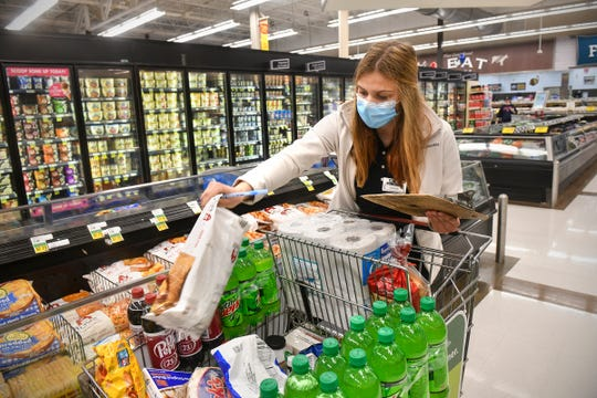 MaKenzi Schmitz collects items for a pick-up order  Wednesday, April 29, 2020, at the Pinecone Road Coborn's Marketplace in Sartell.