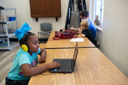 Kids attending childcare at the YMCA of the Treasure Coast are keeping distance from each other by sitting apart, including Messiah Jefferson, 7, of Stuart, who works on a laptop Tuesday, April 28, 2020, at the YMCA campus in Stuart. Because of the effects from the coronavirus pandemic, there has been a 30% decrease in memberships, according to Senior Vice President Charlene Lyons, but locations across the Treasure Coast continue offering childcare services for essential workers who can't stay at home with their children while schools are closed.