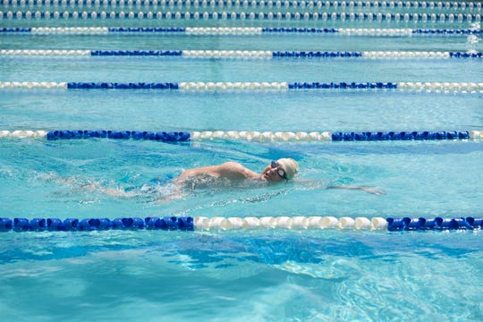 Terry Wilson, of Jensen Beach, swims laps in the nearly empty pool at the YMCA of the Treasure Coast on Tuesday, April 28, 2020, in Stuart. Although gyms are closed under Gov. Ron DeSantis' Safer at Home executive order, YMCA staff consulted with the Martin County Department of Health to reopen the pool to members on a reservation-only basis limited to no more than eight people at a time. Swimmers enter the pool through a gate and never go inside the building, are assigned a lane ahead of time and use alternating starting ends.