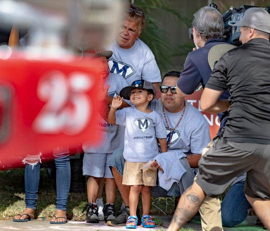 Mateo Martinez, 3, waves to passing fire engines during a welcome home parade for him on Wednesday, April 29, 2020. The boy nearly drowned last week in a backyard pool but is expected to make a full recovery thanks to CPR given by his father and a neighbor.