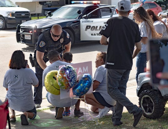 Visalia Police Officer Ryan Lasalde gives a hat and t-shirt to Mateo Martinez, 3, during a welcome home parade for him on Wednesday, April 29, 2020. The boy nearly drowned last week in a backyard pool but is expected to make a full recovery thanks to CPR given by his father and a neighbor.