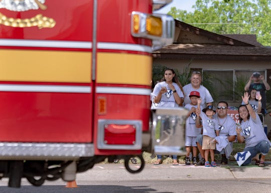 Mateo Martinez, 3, and his parents wave to passing fire engines during a welcome home parade for him on Wednesday, April 29, 2020. The boy nearly drowned last week in a backyard pool but is expected to make a full recovery thanks to CPR given by his father and a neighbor.