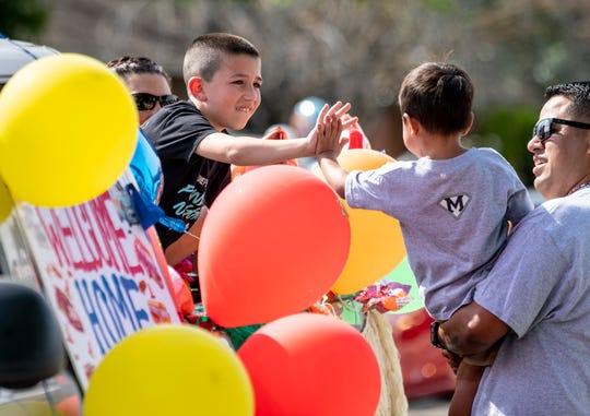 Ryan Martinez, right, holds his son Mateo Martinez, 3, to greet supporters in a welcome home parade for the boy on Wednesday, April 29, 2020. Mateo nearly drowned last week in a backyard pool but is expected to make a full recovery thanks to CPR given by his father and a neighbor.