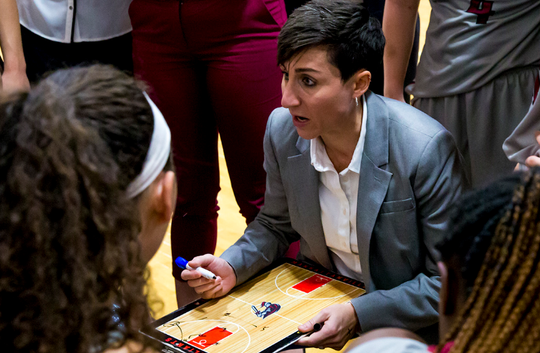 Manhattanville head coach Kate Vlahakis draws up a play for her team during a time out.