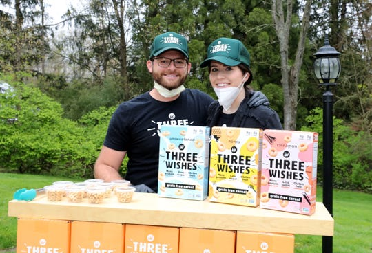 """Ian and Margaret Wishingrad of Scarsdale, have created a new cereal line called """"Three Wishes"""". Here they are pictured in their driveway, April 29, 2020, where over the weekend, they passed out samples in their """"drive-thru"""" U shaped driveway."""