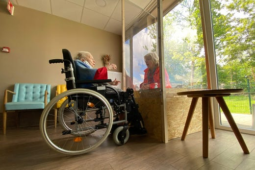 A visitor in a plexiglass lock talks to a resident at Les Jardins d'Astrid, a rest home in Maurage, La Louviere, on April 29, 2020, as the visits to residents of rest homes are possible from today in Wallonia.