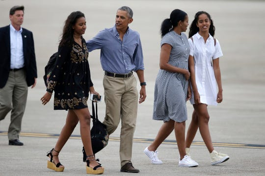 Barack and Michelle Obama, with their daughters, Sasha, far left, and Malia, prepare to board Air Force One in Bourne, Mass., on Aug. 21, 2016, after vacationing on Martha's Vineyard.