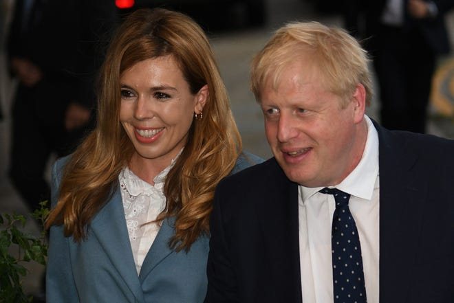 In this file photo taken on September 28, 2019 Britain's Prime Minister Boris Johnson walks with his partner Carrie Symonds as they arrive at The Midland, near the Manchester Central convention complex in Manchester, northwest England.