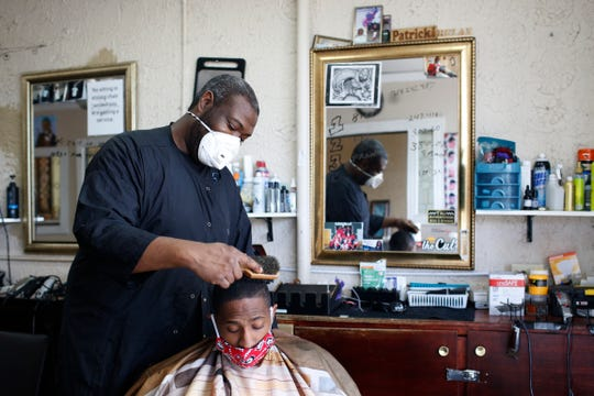 Barber Patrick Watkins of Jet Cuts & Styles finishes up a haircut on Darrell Stevens at the reopened barbershop in Athens, Ga, on Friday, April 24, 2020.