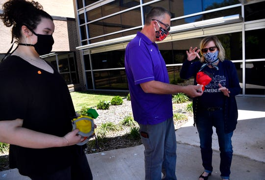 Megan Boren (left) watches as her uncle, Dan Boren, the director of engineering at Roscoe Collegiate High School, holds one of the reusable masks made by students at Roscoe and at ATEMS. The masks were delivered Thursday to Abilene Regional Medical Center.
