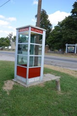 A typical 1950s telephone booth, complete with a hanging telephone.