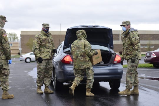 Members of the Ohio National Guard load food into a vehicle as part of a drive-thru food distribution offered by Second Harvest Food Bank at Bucyrus High School in late April. A similar event is scheduled for Friday at Galion Middle School.