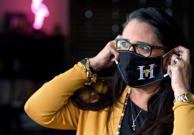 Susana P. Garza puts on a face mask with the Hebbronville High School logo, Wednesday, April 29, 2020, in Hebbronville, Texas. Garza is the superintendent of schools for Jim Hogg county and says the masks were made by one of the student's grandparents.