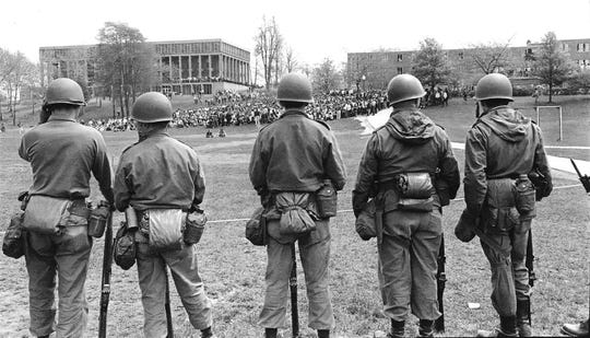 National Guardsmen stand in line and look across Kent State's Commons area to Taylor Hall and a gathering of student protesters on May 4, 1970.