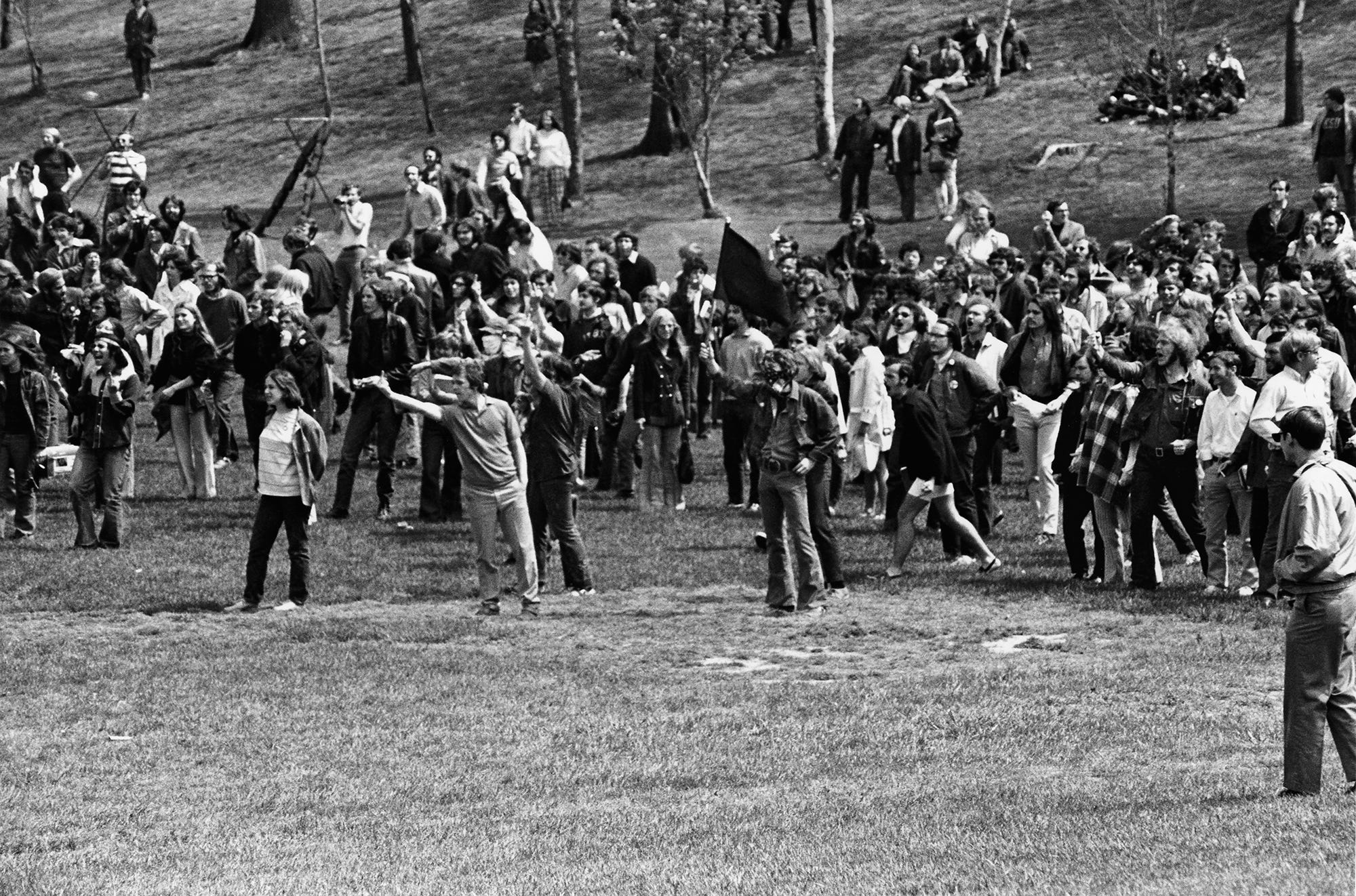 Protesters and bystanders at the edge of the Commons below Taylor Hall gesture and yell at the Ohio National Guardsmen across the field. At left, wearing a headband, is Jeffrey Miller; Mary Ann Vecchio is looking to the left wearing a black t-shirt and dark pants, partially behind the young man flipping the bird.