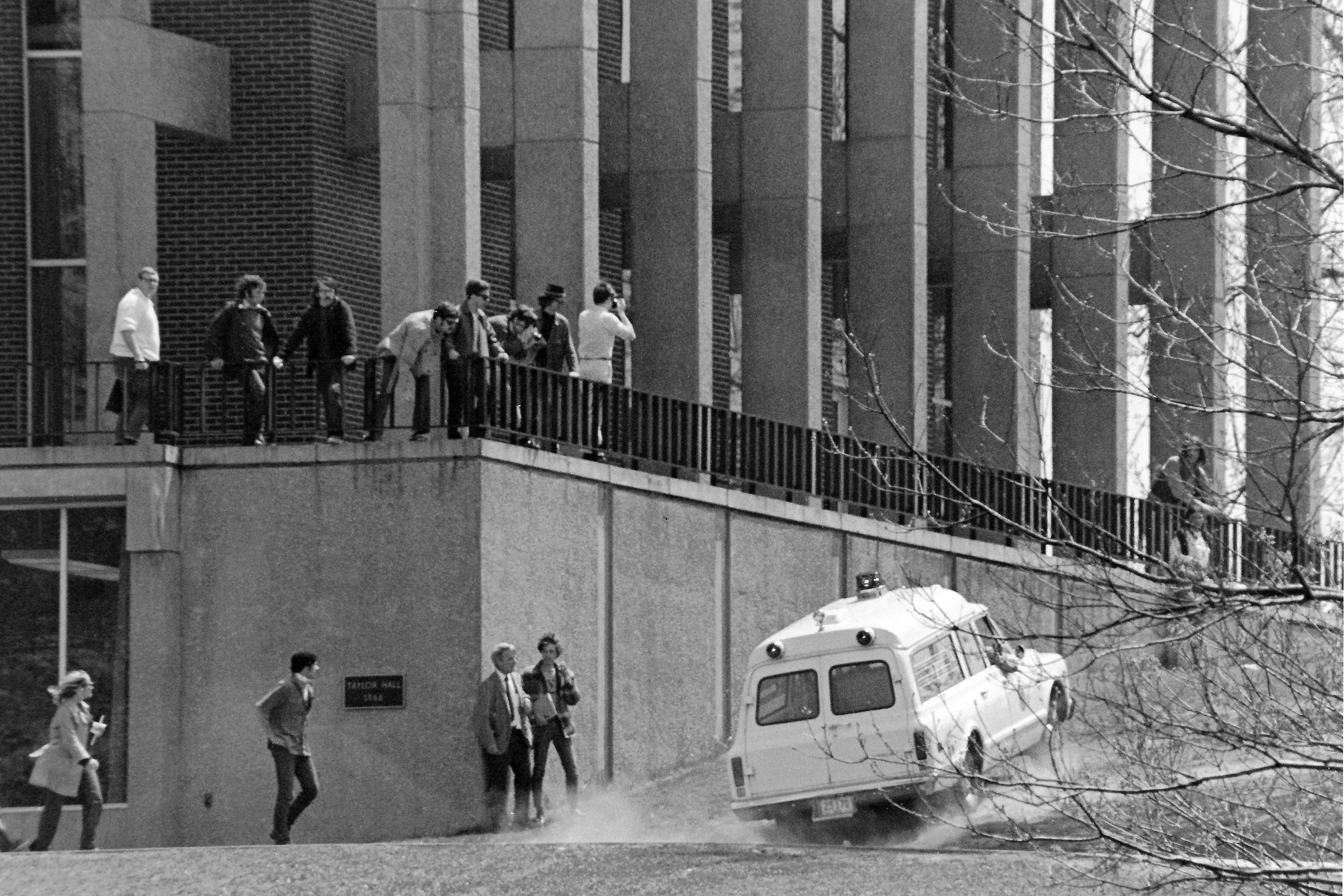 An ambulance drives away up the hill next to Taylor Hall as a small group of onlookers watches.