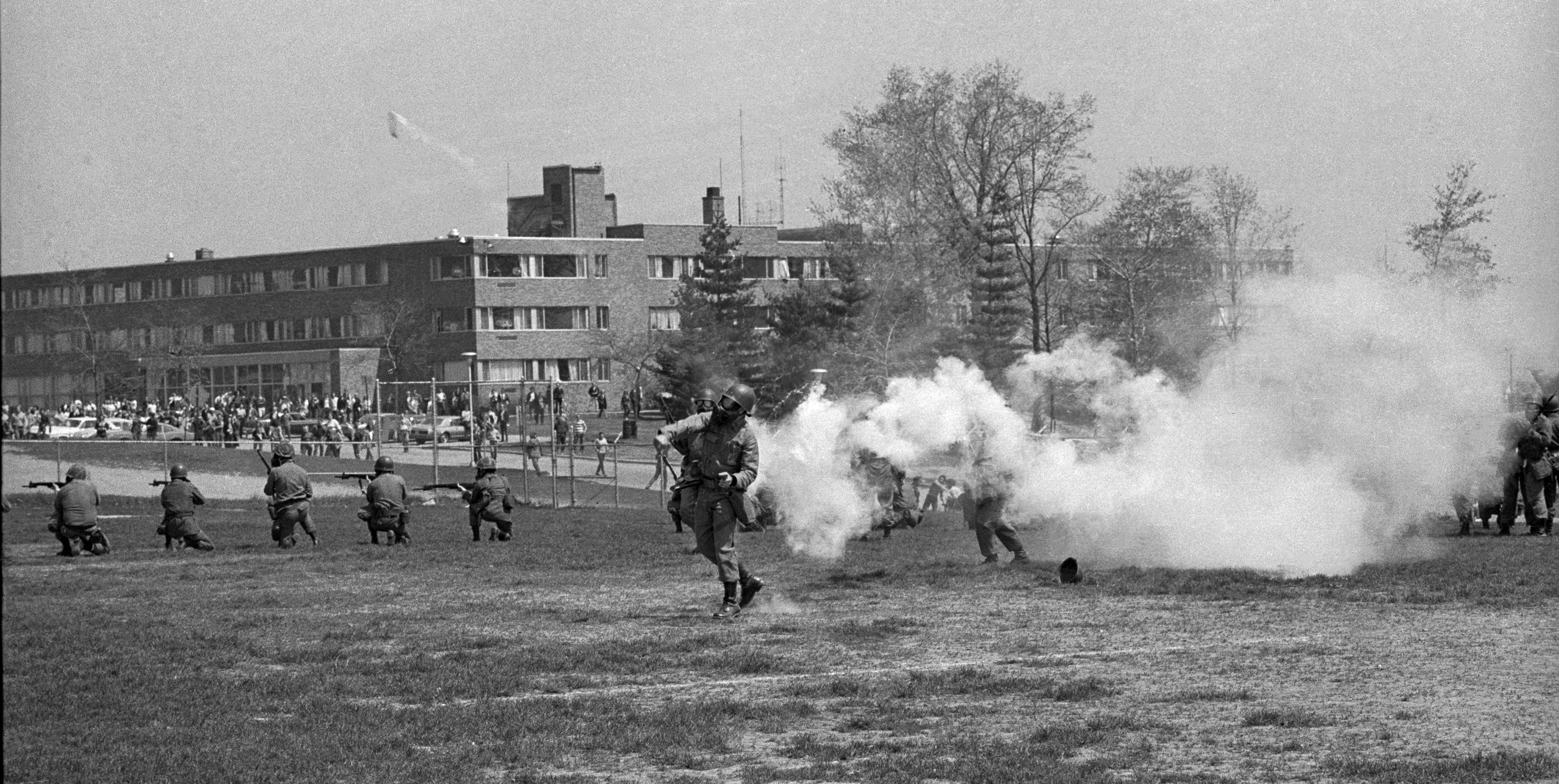 An Ohio National Guardsmen throws a tear gas canister toward protesters at Kent State.