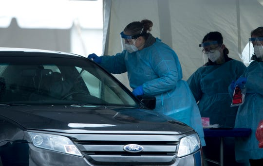 Healthcare workers hands a patient a COVID-19 test at a drive through set up by Kroger at the Dunham Recreation Center  in Westwood. The testing site set up by Kroger in Hamilton County is for people with symptoms as well as health care workers and first-responders.