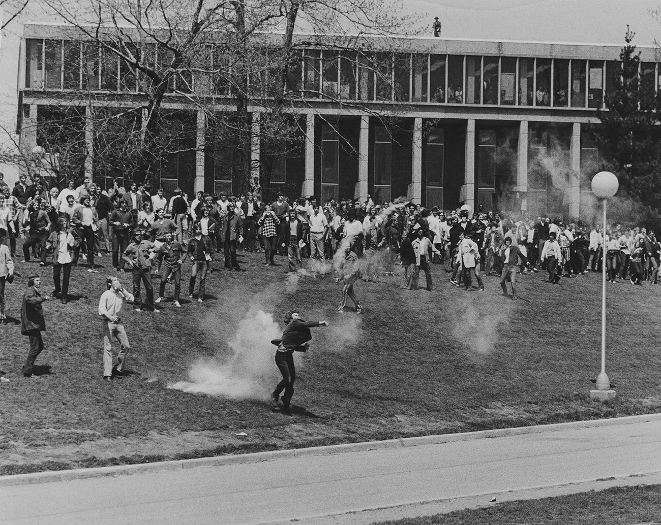 A student throws back a tear gas canister below Taylor Hall on the Kent State campus on May 4, 1970. Protesters clashed with Ohio National Guard units that were sent to campus to quell unrest.