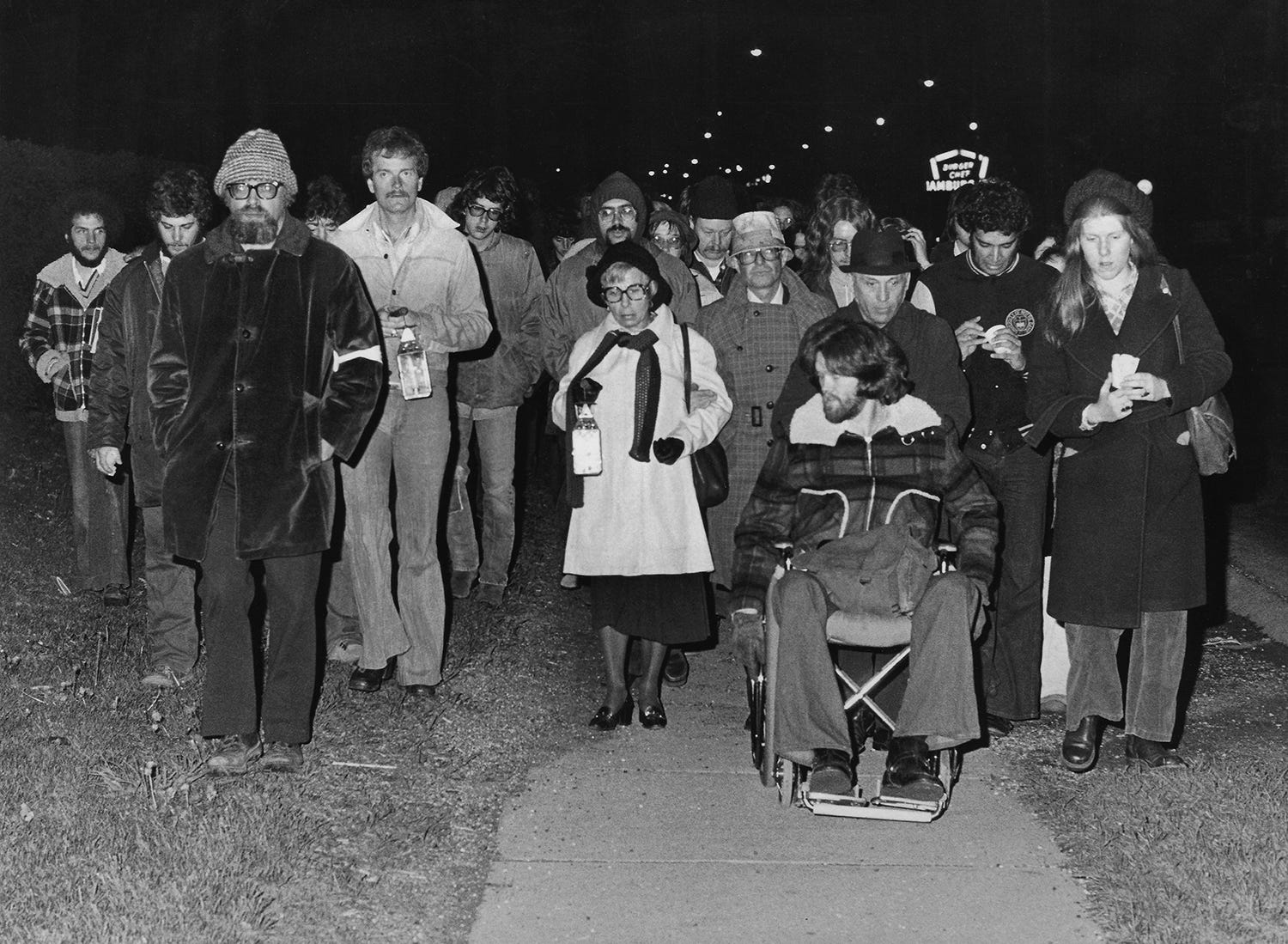 Professor Jerry Lewis (left, with beard), Elaine Holstein, mother of slain student Jeffrey Miller (center in white coat), and survivor Dean Kahler (in wheelchair) participate May 3, 1976, in the annual candlelight vigil march to commemorate the 1970 shootings on the Kent State campus.