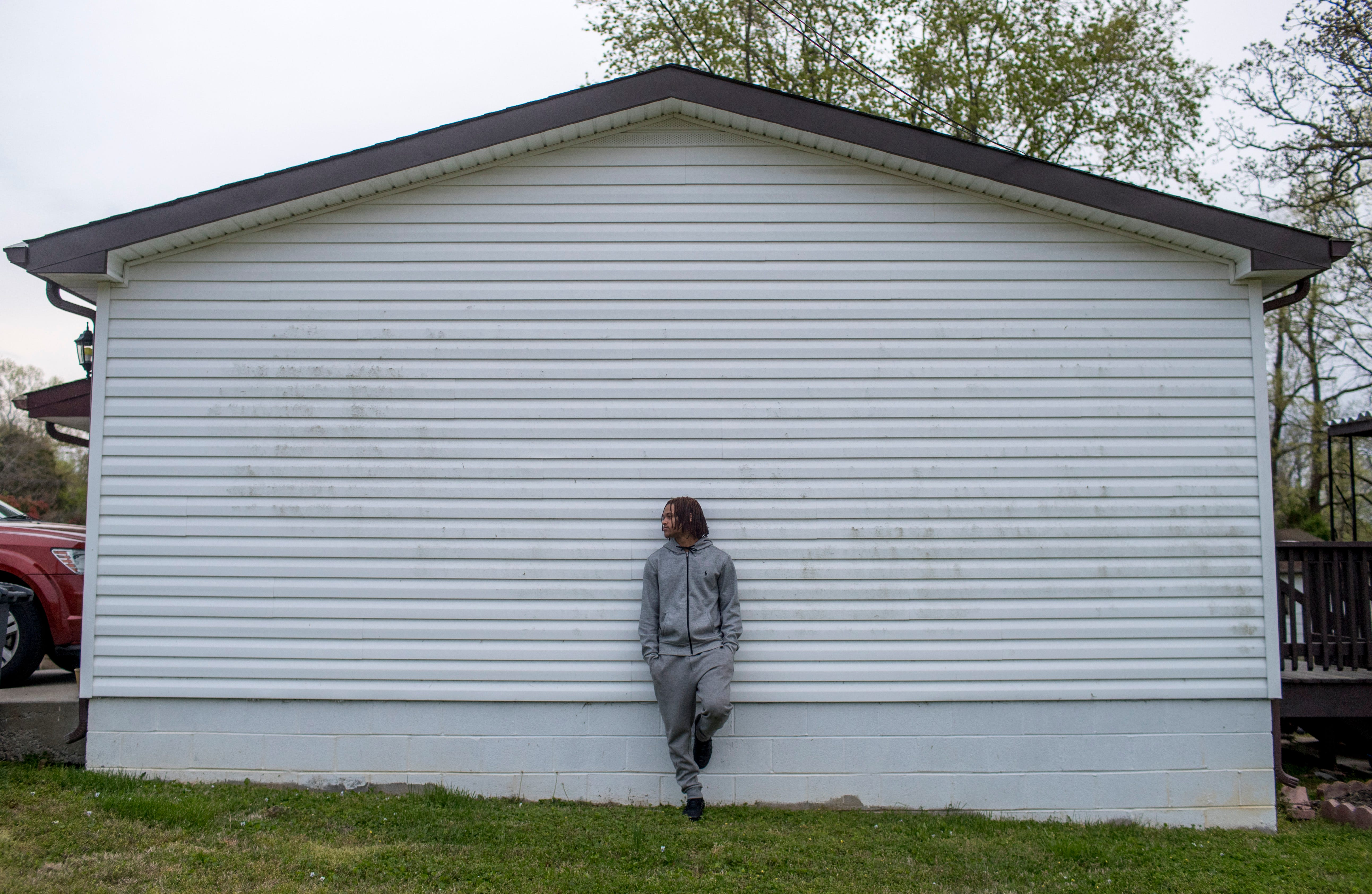 Christopher Williams, a Kenwood senior who will miss out on his last season of track, leans against the outside wall of his home in Clarksville, Tenn., on April 3, 2020.