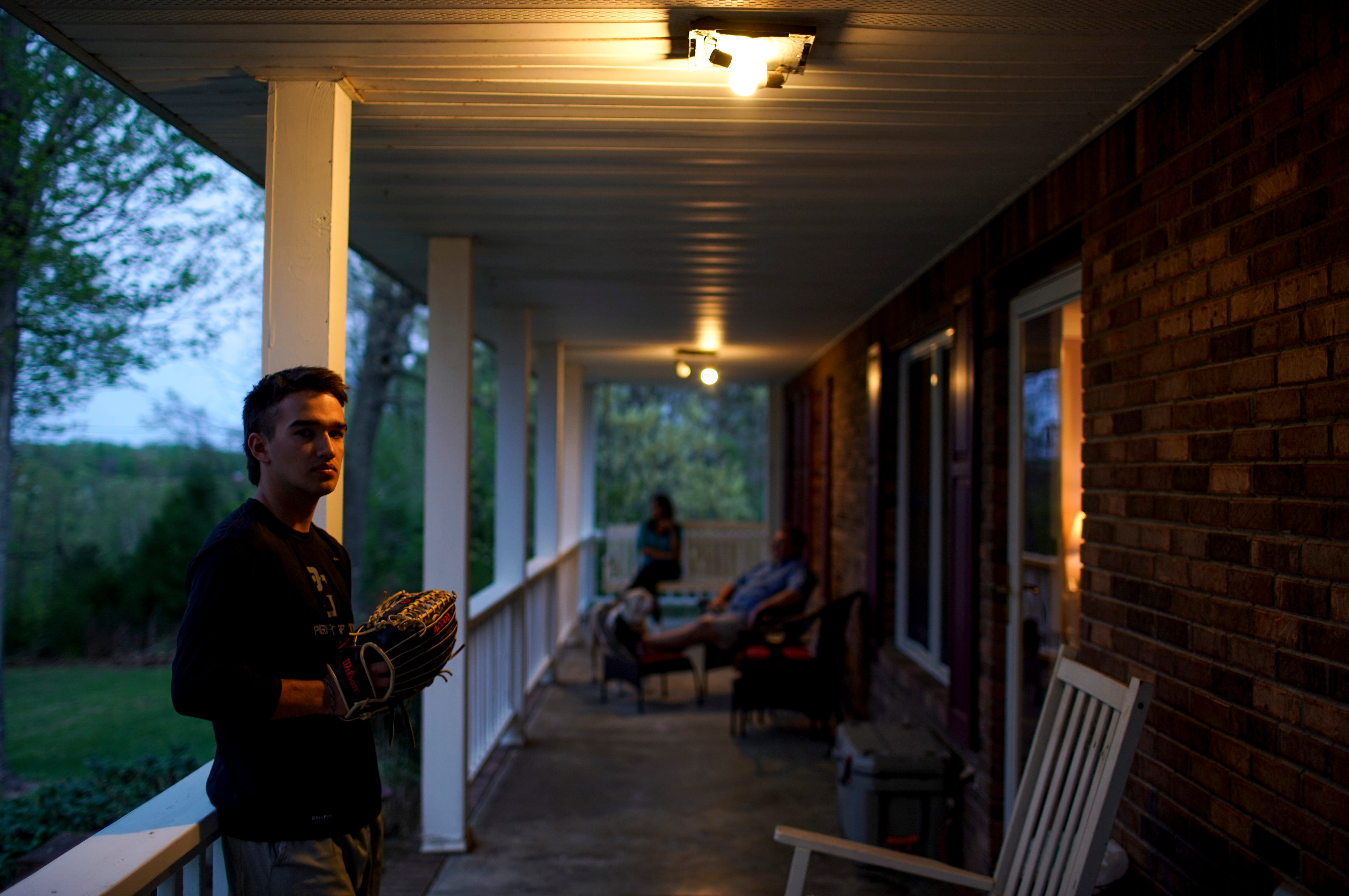 Cody Kirkland, a senior from Northwest who won't be able to play his last year of baseball because of the coronavirus pandemic, holds his glove on the front porch of his home in Indian Mound, Tenn., on April 11, 2020.