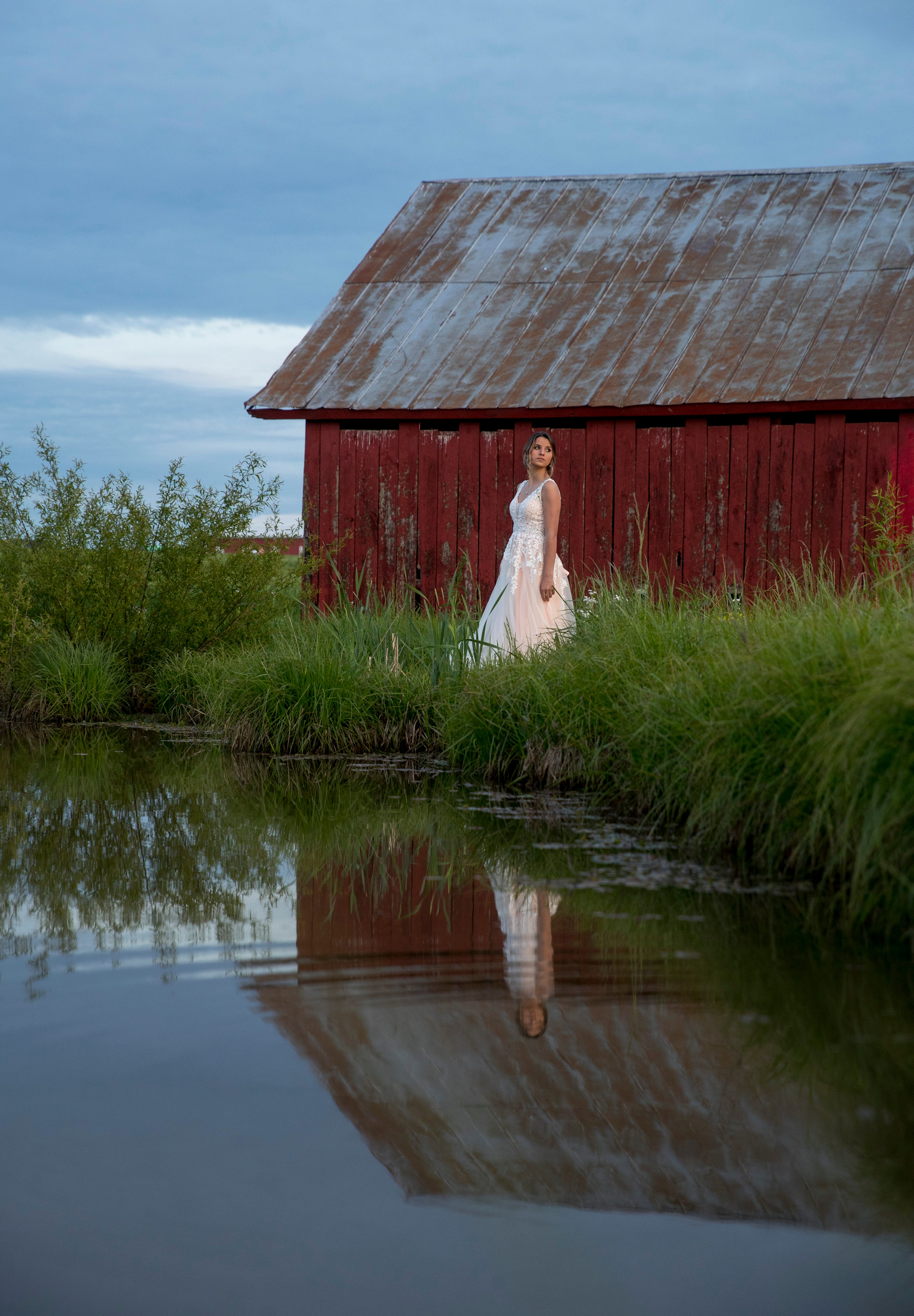 Arie Milam, a senior softball player for Clarksville High and 2019's homecoming queen, stands at the edge of a pond near her family's Cedar Hill, Tenn., property in the dress she would have worn to prom on April 27, 2020.
