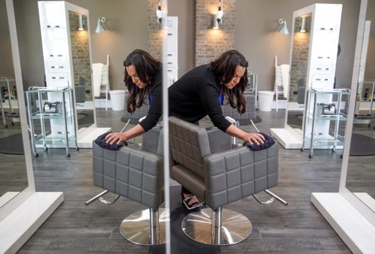 Owner Rachel Buchanan wipes down a salon chair in preparation for opening back up in early May at Meraki Hair Studio in Clarksville, Tenn., on April 30, 2020.