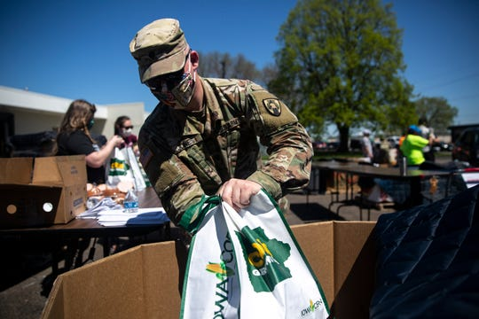 Specialist Marcus Jones, with the Iowa National Guard, helps bag food to be handed out to a waiting line of cars outside the Food Bank of Iowa on April 30 in Des Moines, Iowa. Indianola's food pantry distribution is May 19.