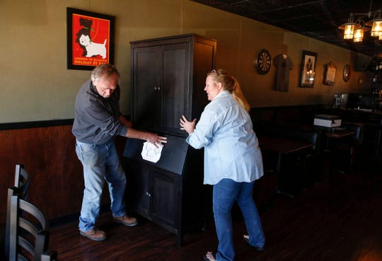 Marvin Gibbons and his wife, Lori Hayden, moves a cabinet while preparing their pub, The Groggy Dog, for a safe social distance arrangement prior to Friday's opening in Indianola. Seventy-seven counties in Iowa will reopen on Friday.