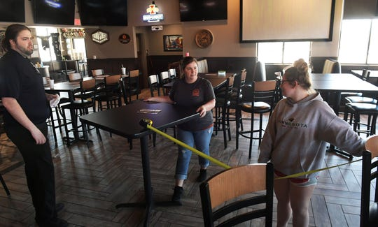 Employees of The Boulder Tap House restaurant  Zach Williams, Lindsey Galvin, and Kiley Wharton measure table to table for setting arrangements following social distance guidelines Thursday, April 30, 2020, in Ames, Iowa, getting ready to open their business on Friday, May 1, 2020.