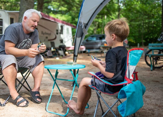 A dad and son play Uno at Otsego Lake State Park the summer of 2019.