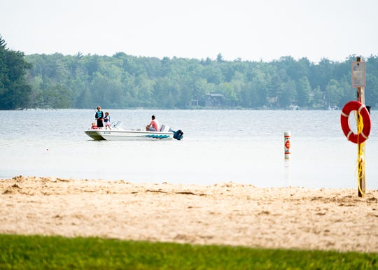 A family fishes of a boat on Interlochen State Park in the summer of 2019.