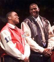 Former Pistons guard Isiah Thomas, left, jokes with former Lakers guard Magic Johnson during halftime ceremonies of the NBA All-Star Game, Feb. 9, 1997, in Cleveland. Both were named members of the 50 greatest players in NBA history.