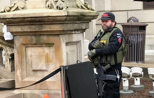 Tom Scillian, 59, of Utica, a member of the Michigan Liberty Militia, guarded the steps that led to the podium in front of the Capitol Thursday. He legally carried what he said was a loaded AR-15 rifle.