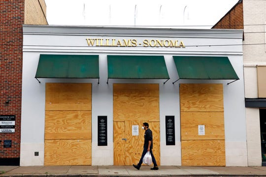 A man walks in the Shadyside shopping district of Pittsburgh past a Williams-Sonoma store that is boarded up temporarily due to social distancing mandates on Wednesday, April 29, 2020.