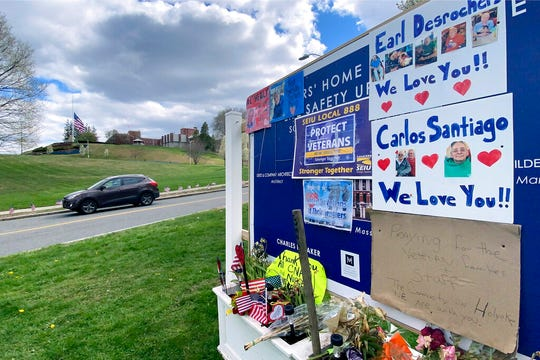Tributes to veterans cover a sign Tuesday, April 28, 2020, near an entrance road to Soldiers' Home in Holyoke, Mass.
