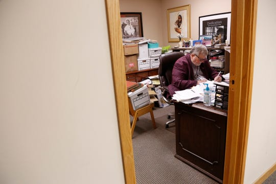 In this Dec. 1, 2019, file photo the Rev. Philip Schmitter prepares for a sermon in his office at Christ the King Catholic Church in Flint.