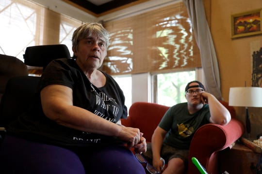 Debra Mize, left, and her son, Zach Stafford, watch a livestream of the daily coronavirus briefing by Illinois Gov. J.B. Pritzker on a television inside their home in Belleville, Ill. The pair say they are consuming hours of news each day in various formats about the coronavirus.