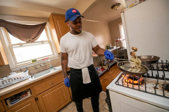 Chef Desean Washington-Jones, who started a catering business called D Street Creations after being laid off due to COVID-19, prepares a birthday meal for clients in his Detroit home, April 30, 2020.