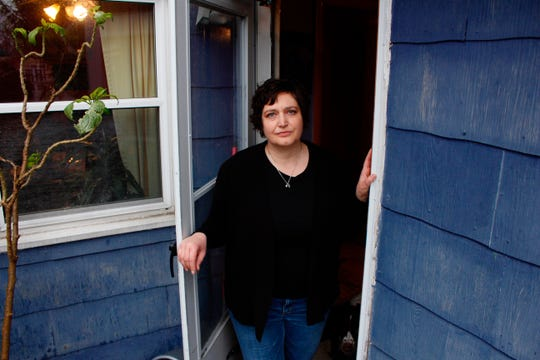 Julie Hitchcock stands in her back doorway in Milwaukee. Hitchcock, 49, said she worries about getting sick or unknowingly infecting someone else, anxiety that's heightened because she was on a ventilator for two weeks last fall after developing pneumonia.
