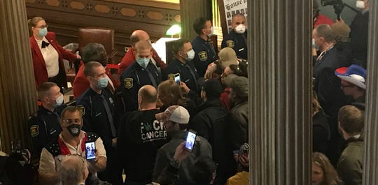 Protesters gather outside the Michigan House chamber on Thursday, April 30, 2020. The demonstrators demanded access to the House chamber as State Police troopers blocked the entrance, which is usually reserved for House members and staff.